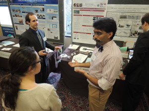 Ankur Mehta, center, of MIT, explains his printable robots to an attendee at the 2014 CNSF Exhibition.